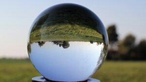 Es steht eine Glaskugel auf der Wiese und das Bild in ihr steht auf dem Kopf.
