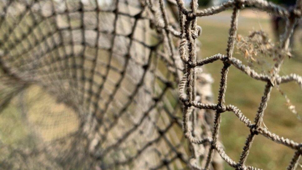 Es ist ein Ausschnitt eines Fischernetzes zu sehen.